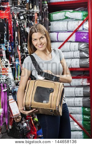 Smiling Woman Showing Pet Carrier In Store