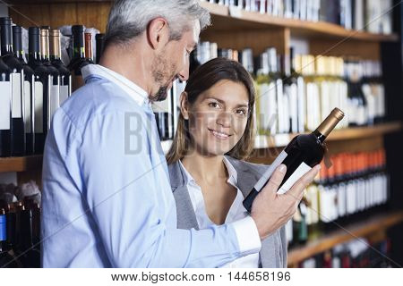 Woman Standing With Man Holding Wine Bottle In Shop