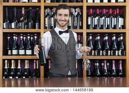 Bartender Holding Red Wine Bottle And Glass In Shop