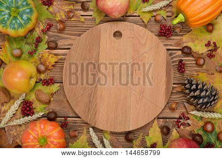Autumn leaves apples pumpkins and nuts on a brown background