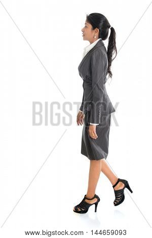 Full length side view of African American businesswoman walking isolated on white background.