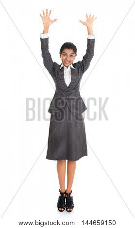 Full length portrait of Indian businesswoman arms raised, standing isolated on white background.