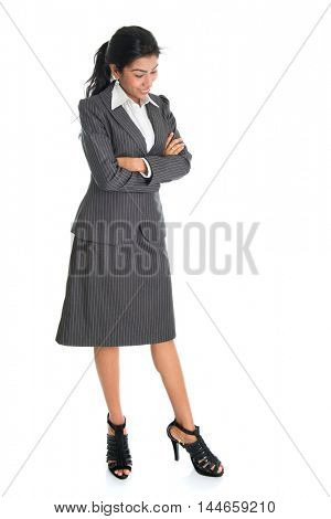 Full length portrait of African American businesswoman looking downward, standing arms crossed isolated on white background.