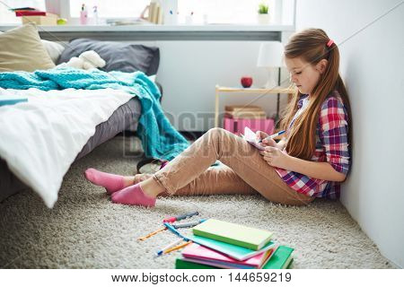 Teenage long-haired girl sitting thoughtful on floor in her bedroom and writing in notebook