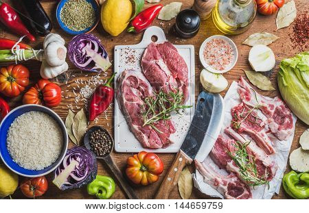 Ingredients for cooking dinner. Raw uncooked lamb meat assortment, rice, oil, spices and vegetables over wooden background, top view