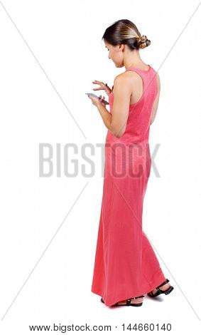 back view of standing young beautiful woman using a mobile phone or tablet computer. girl watching. slender woman in a long red dress dials number on phone.