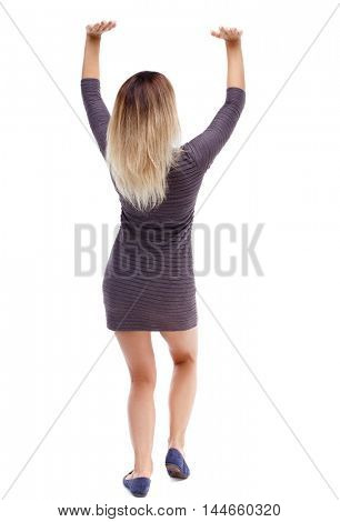 back view of woman protects hands from what is falling from above. Isolated over white background. Blonde in violet short dress holding a weight over her head.
