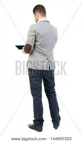 back view of business man uses mobile phone. bearded man in a gray jacket, working on the tablet.