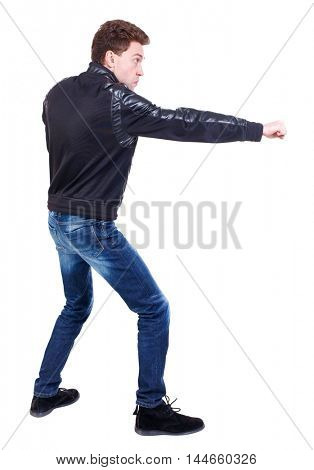 back view of guy funny fights waving his arms and legs. Curly guy in a black leather jacket fun waving his arms.