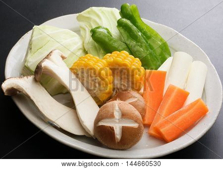Fresh vegetables for hot pot with corn mushroom carrot radish cucumber and cabbage on white platter