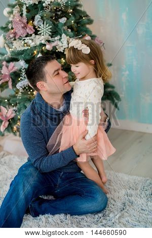 Happy father and daughter are playing in front of Christmas tree