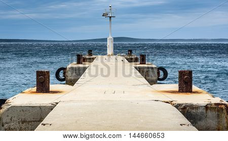 Old Pier With A Lighthouse Beacon And Calm Sea.