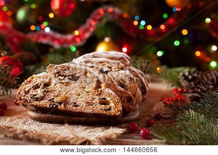 Traditional Dresdner German Christmas cake Stollen with Marzipan, Berries Nuts, Cinnamon, Raising on a rustic wooden festive table. Holiday xmas celebration decorations.