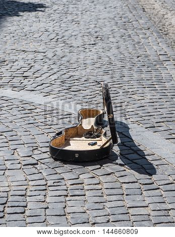 Open case of the guitar on the old cobblestones