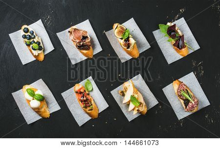 Italian crostini with various toppings on white baking paper over black plywood background, top view