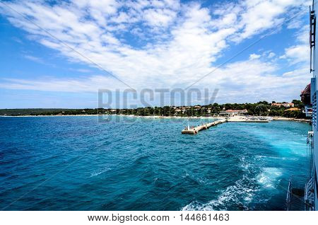 Ship is leaving a port with blue sea and a pier. Landscape photo of ships side as it is leaving idyllic port leaving a wake of water behind.