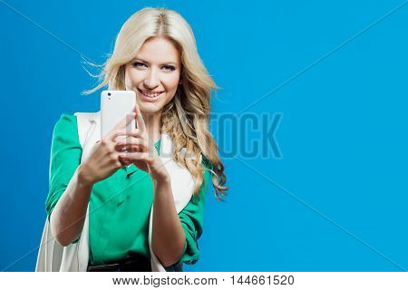 Portrait of a young confident blonde, casual style, blue background