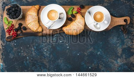 Breakfast set. Freshly baked croissants with garden berries and coffee cups served on rustic wooden board over dark grunge plywood backdrop, top view, copy space