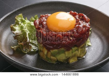 Avocado tartare stab Sakura beef meat with red egg and lettuce on black platter