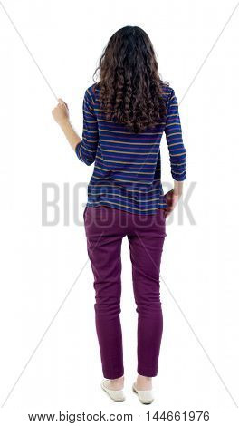 back view of standing young beautiful woman. Long-haired curly girl in a blue striped jacket presses squeezed his hand into a fist.