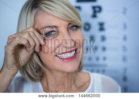 Portrait of smiling female patient looking through magnifying glass in clinic