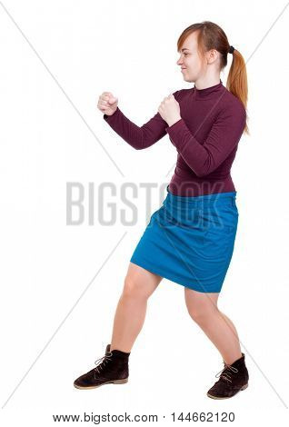 skinny woman funny fights waving his arms and legs. Girl with red hair tied in a ponytail in a boxing rack.