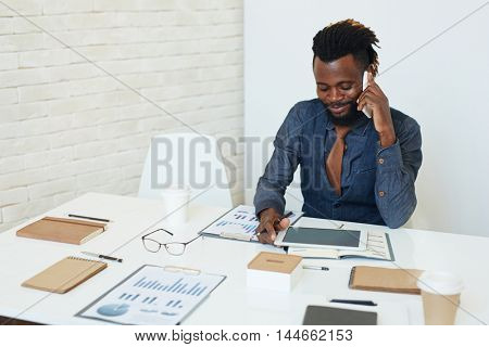 Charismatic young African American businessman busy working and talking on phone in office room, documents, charts and tablet on desk before him