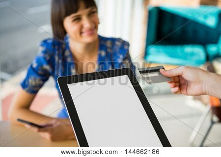 Close-up of hand holding a credit card next to the digital tablet in the coffee shop