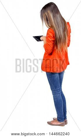 back view of standing young beautiful woman using a mobile phone or tablet computer. girl watching. girl in a red jacket thumb drives on the tablet.