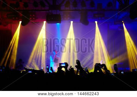 Fans in crowd raising hands up cheering in front of stage at music concert, admiring great performance of young singer in bright lights and filming it with smartphones