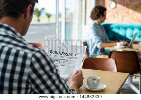Rear view of man reading a business newspaper in coffee shop