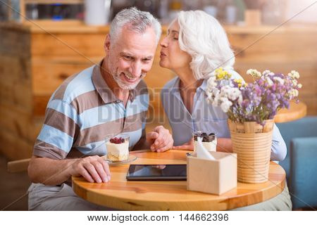 With love. Positive senior woman kissing her smiling husband while resting in the cafe