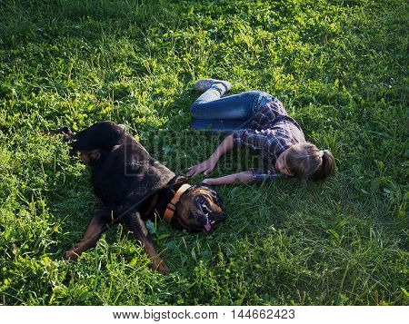 Girl Plays With A Huge Rottweiler Dog On The Green Grass
