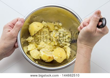 Kneading potatoes by hands in iron stew in the kitchen