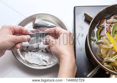 Salting sardine fish for cooking in the kitchen