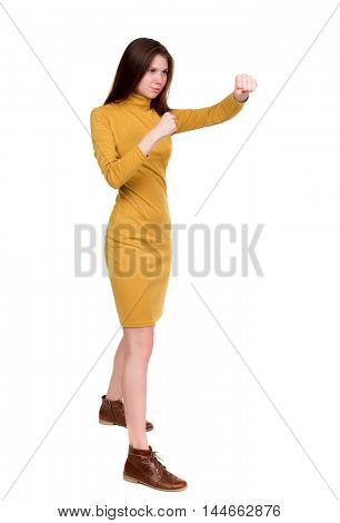 skinny woman funny fights waving his arms and legs. Long-haired brunette in a mustard-colored dress in boxing.