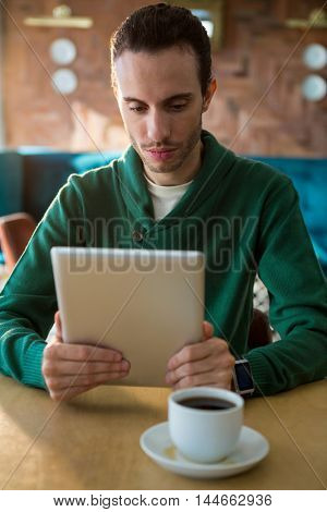 Man using digital tablet and coffee cup on table in coffee shop