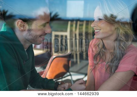 Smiling couple interacting with each other in coffee shop