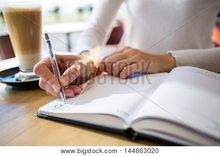 Mid section of woman writing in diary at cafeteria