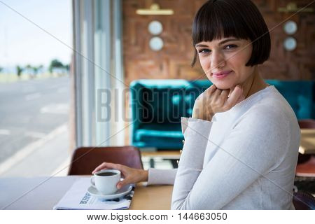 Portrait of smiling woman sitting in cafeteria