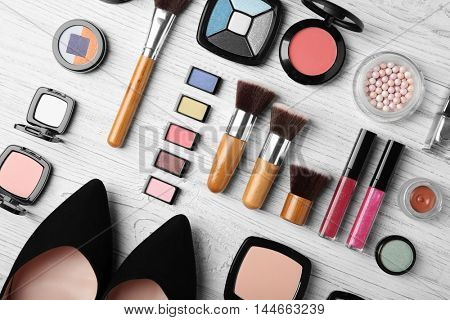 Makeup products, brushes and female shoes on a wooden background