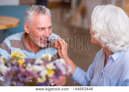 Try it. Cheerful delighted senior couple sitting at the table and eating dessert while resting together