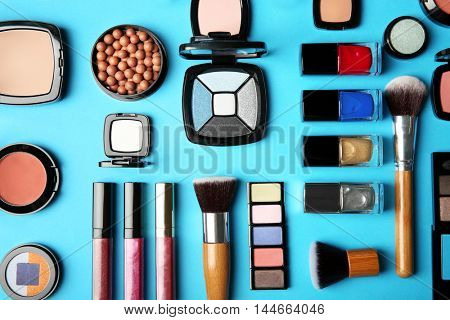 Makeup products and brushes  on a blue background