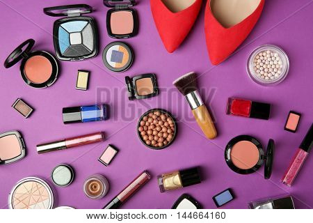 Makeup products, brushes and female shoes on a purple background
