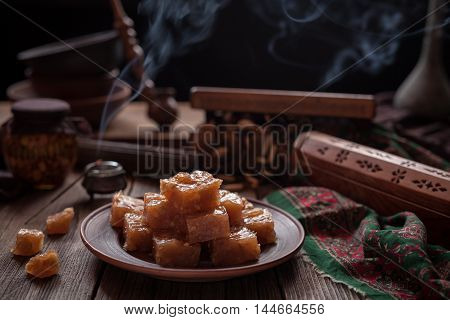 Turkish Still life, Arabic traditional dessert rahat lukum, lokum powdered with sugar, eastern candy. Seasonal and holidays ramadan, seker bayram concept. Smoky hookah atmospheric.