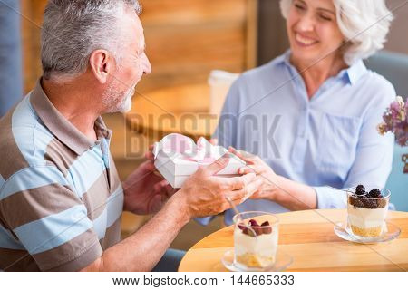 Have a nice celebration. Cheerful senior loving couple sitting at the table and holding present while resting in the cafe