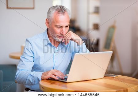 Serious attitude. Pleasant delighted senior man using laptop and sitting at the table while spending time in the cafe