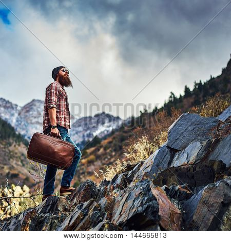 bearded traveler with luggage climbing mountain top