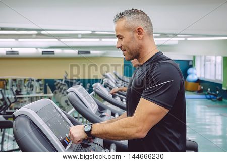 Portrait of handsome man setting control panel of treadmill for training in fitness center. Sport and technology concept.