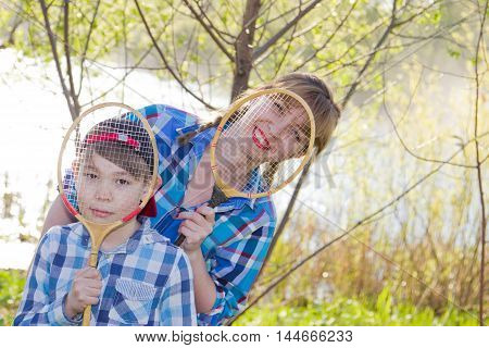 Mother and son with a badminton racket on the banks of the river in the spring